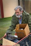 9485844-homeless-man-wearing-an-old-army-coat-pushes-a-shopping-cart-holding-his-possessions