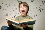 Boy_reading_book_with_letters_flying_out