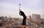 A man with a sledgehammer smashes concrete to recycle steel bars in China